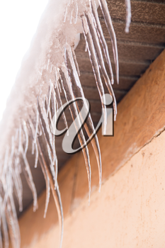 icicles on a roof of a house in winter