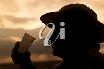 silhouette of a man drinking water on the sunset background