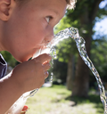 boy drinking water outdoors