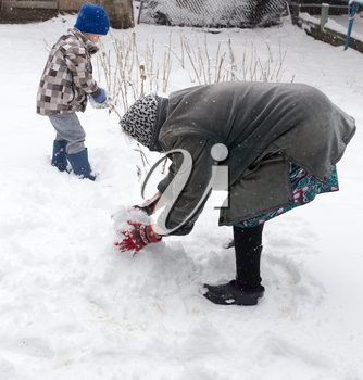 a boy with his grandmother playing in the snow