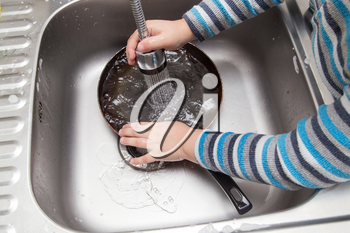 a boy washing dishes in the kitchen