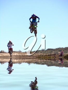Royalty Free Photo of Motorcycles Jumping Over Water