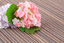 Colorful artificial flowers on cloth background, closeup picture.