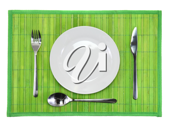 Table serving-knife,plate,fork on  green colour background.