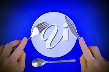 Table serving-knife, fork in hands on blue background.