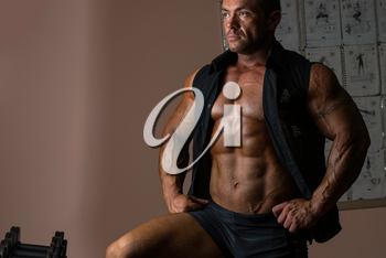 male bodybuilder posing in black shirt without sleeves