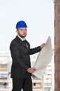 Portrait Of Construction Master With Blue Helmet And Blueprint In Hands