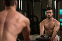 Male Bodybuilder Doing Heavy Weight Exercise For Back In Modern Gym