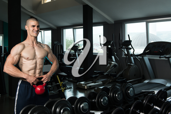 Young Man Working With Kettle Bell In A Gym
