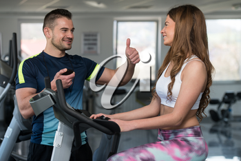 Personal Trainer Showing Ok Sign To Client - Woman Exercising Her Legs Doing Cardio Training On Bicycle