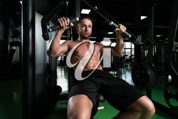 Young Strong Man In The Gym And Exercising Chest On Machine - Muscular Athletic Bodybuilder Fitness Model Exercise