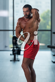 Portrait Of A Young Physically Fit Hispanic Man Showing His Well Trained Abdominal Muscles - Muscular Athletic Bodybuilder Fitness Model Posing After Exercises