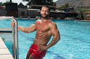 Portrait Of A Wet Sexy Muscular Man Standing In Swimming Pool