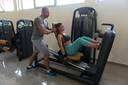 Young Adult Woman Working Out In Gym - Doing Legs Exercise On Machine With Help Of Her Personal Trainer