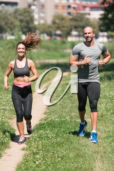 Young Couple Running In Wooded Forest Area - Training And Exercising For Trail Run Marathon Endurance - Fitness Healthy Lifestyle Concept