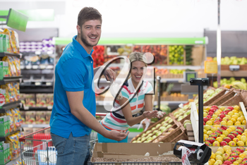 Beautiful Young Couple Shopping For Fruits And Vegetables In Produce Department Of A Grocery Store - Supermarket - Shallow Deep Of Field