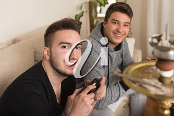 Two Men Competitive Friends Playing Video Games and Excited Happy Cheerful at Home