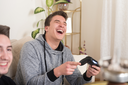 Two Brothers or Friends Playing Video Games Together as They Relax on a Couch in the Living Room