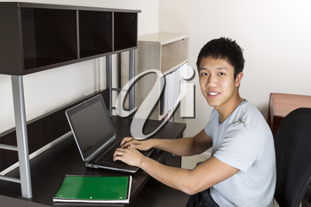 Young man studying at home office for college work with computer and notepad on desk