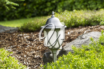 Photo of electric outdoor lamp with post in flower bed with rocks and green in background