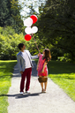 Vertical photo of young adult couple dressed in formal attire looking at several balloons while holding picnic basket with walking path, green grass and trees behind them