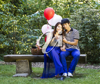 Photo of young adult couple sitting on log bench, looking forward, with glasses filled with red wine being held in their hands with balloons, green grass and trees in background