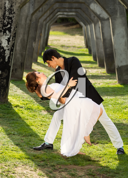 Vertical photo of young adult couple dancing outdoors together underneath a structured column wall in background