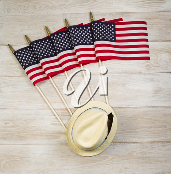 Overhead view of five United States of America flags and hat placed on faded white wood.