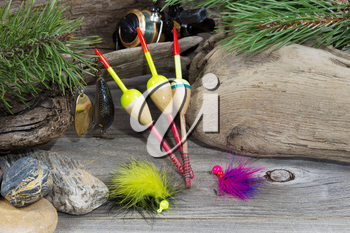 Horizontal image of fishing equipment consisting of floats, reel, lures, and feathered flies resting against aged driftwood, evergreen tree branches and rocks