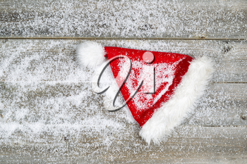 Horizontal image of Christmas Santa hat, covered with snow, on rustic wooden boards