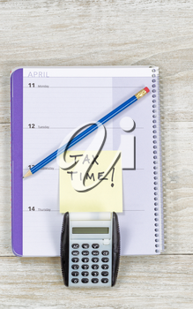 Vertical top view of an office wooden desktop with small calendar, calculator and sharpen blue pencil with reminder of doing Tax Return.