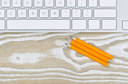 Office desktop with three pencils and keyboard on aged white wood. Top view angled shot in horizontal format with copy space.