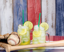 Jar glasses filled with cold lemonade with baseball sporting items.  Faded wooden boards painted red, white and blue in background. Selective focus on upper front jar glass with lime slice.