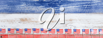 Small USA flags on bottom of red, white and blue rustic boards. Fourth of July holiday concept for United States of America.