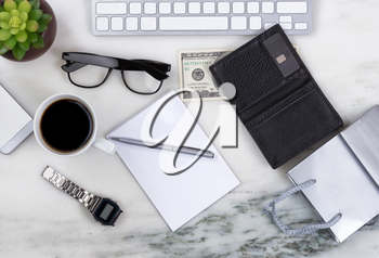 Overhead view of office desktop with computer keyboard, cell phone, shopping bag, wallet, money, pen, paper, reading glasses, coffee and plant on marble surface. Shopping on line concept.