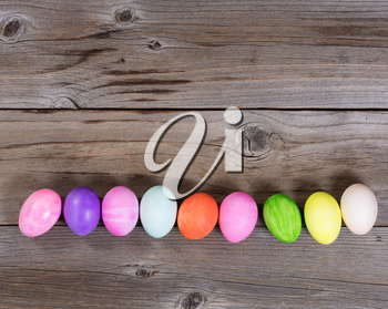 Colorful Easter egg decorations forming lower border on rustic wood.