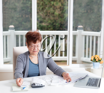 Senior woman looking frustrated while working on her financial bills