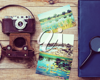 Vintage, very old film camera, magnifying glass, foto and photo album on brown wooden background and space for text. Photo with retro filter effect.