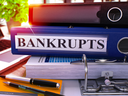 Bankrupts - Blue Office Folder on Background of Working Table with Stationery and Laptop. Bankrupts Business Concept on Blurred Background. Bankrupts Toned Image. 3D Render.