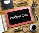 Budget Cuts Handwritten on Red Chalkboard. Top View Composition with Small Chalkboard on Working Table with Office Supplies Around. Budget Cuts Concept on Small Chalkboard. 3d Rendering.