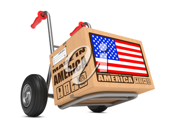 Cardboard Box with Flag of USA and Made in America Slogan on Hand Truck White Background. Free Shipping Concept.