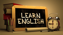 Learn English Concept Hand Drawn on Chalkboard. Blurred Background. Toned Image.