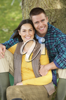 Couple sitting against tree trunk
