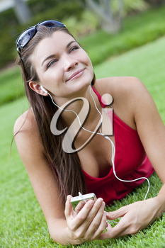 A beautiful young brunette woman lying down outside listening to music on her MP3 player