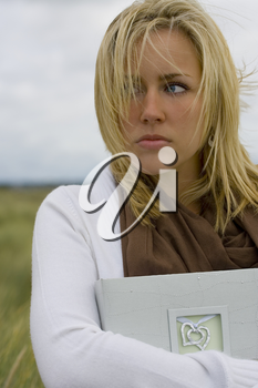 A beautiful blond haired blue eyed young woman stands amid long grass on a windswept headland clutching a book of memories