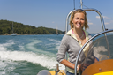 A stunningly beautiful young woman driving a speedboat and having fun with the Mediterranean coast and yachts in the background