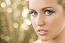 Studio shot of a beautiful young blond model with blue eyes shot against a sparkling gold background.