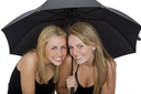 Studio shot of two beautiful young women sharing an umbrella