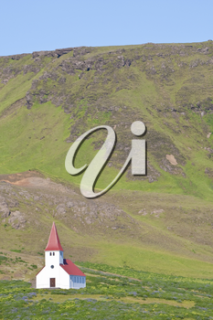 A Lutheran church sits alone on a hillside in Iceland