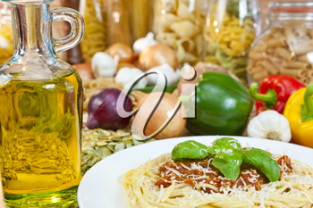 Spaghetti Bolognese with olive oil, Parmesan cheese, basil garnish various Italian pasta and ingredients out of focus in the background.